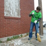 A FHSU The Big Event volunteer helps to clean paint chips after scraping paint at the Hays Community Assistance Center.
