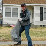 A volunteer helps with the 1st-13th st. sidewalk cleanup.